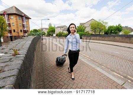 Full length of young businesswoman with luggage while answering cell phone walking on sidewalk