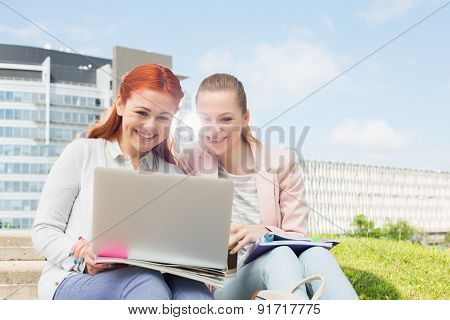 Smiling young university students using laptop with buildings in background