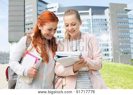 Happy young female college students studying in park with building in background