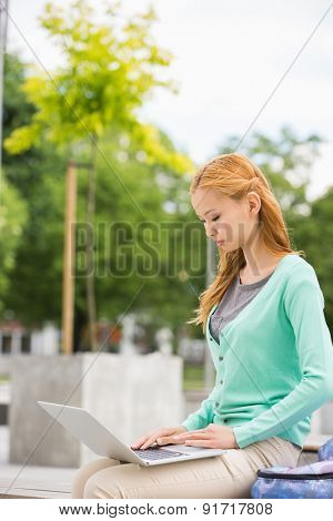 Young woman using laptop at college campus