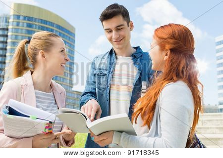 Happy young university students studying outdoors