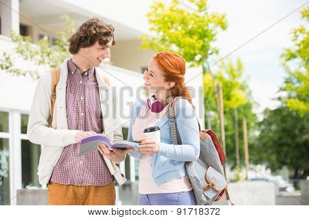 Happy young man and woman studying together at college campus