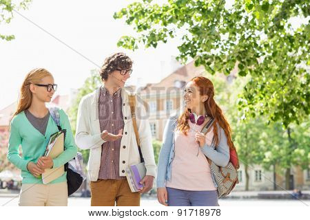 Young college students talking while walking on street