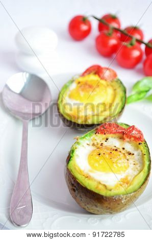 Eggs in the avocado with cherry on the white background
