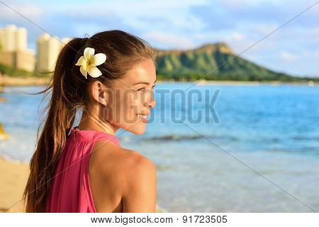 Hawaiian beach woman on Waikiki - beautiful biracial Asian Caucasian girl brunette relaxing and enjoying sun. Oahu, Hawaii, USA.
