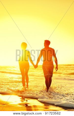 Beach honeymoon couple romantic in love holding hands at beach sunset. Newlywed happy young couple enjoying ocean sunset during travel holidays vacation getaway.