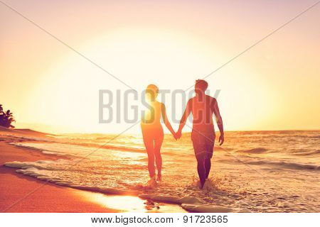 Honeymoon couple romantic in love at beach sunset. Newlywed happy young couple holding hands enjoying ocean sunset during travel holidays vacation getaway.