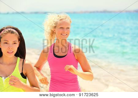women running fitness jogging. Two pretty female fit friends training exercising fitness. Smiling Caucasian woman and focused multiracial Asian woman during workout in sunshine.