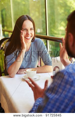 happy loving couple on a date at the restaurant. young beautiful woman laughing and looking at gesticulating man
