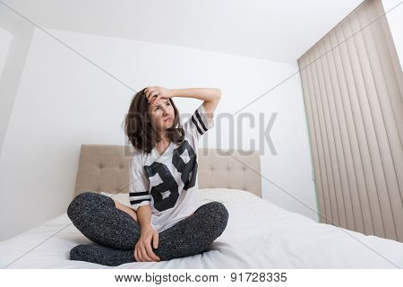 Full length of worried woman looking away in bed