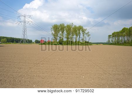 Power line over a field near a city in spring
