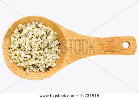 hemp seed hearts on a small wooden spoon isolated on white with a clipping path