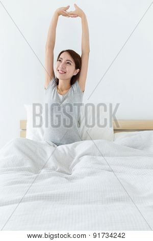 Young woman waking up and stretching hand on bed