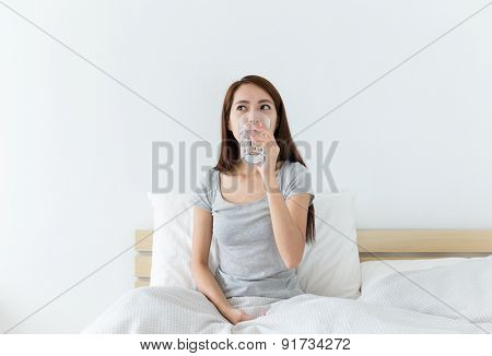 Asian woman drinking a glass of water at living room