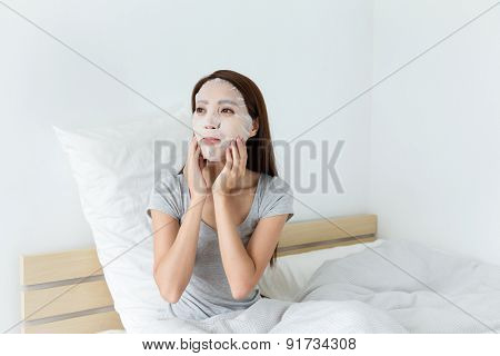 Woman hand adjust the facial mask at bedroom