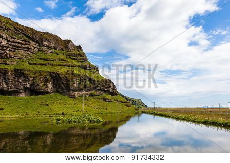 Usual summer in Iceland. Smooth water of the cold lake reflects clouds