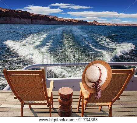 At the stern of the vessel are two deck chairs. On the back of one hanging elegant ladies straw hat. Waves from the boat cut through the Lake Powell on the Colorado River