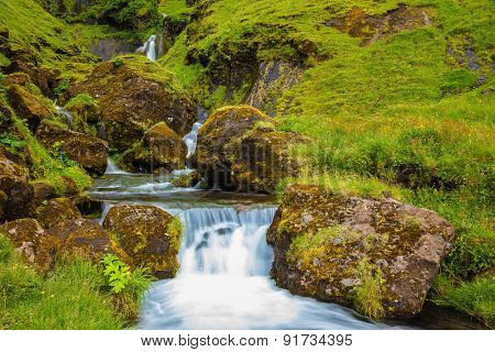 Iceland. Gorgeous cascading waterfall from melting glacier. Basalt mountains covered in green grass and moss