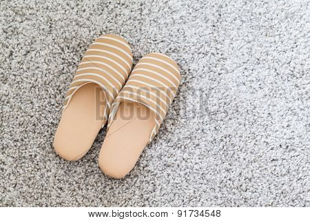 Soft brown color slippers on carpet