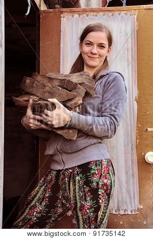 Young Girl Stands With Firewood In Her Hands