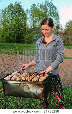 Young Girl Stands At Mangal And Preparing Barbecue