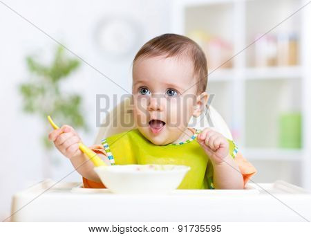 happy baby kid eating food itself with spoon