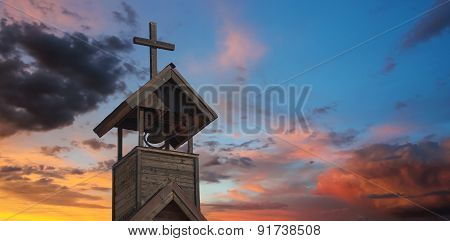 A Bell Tower With Cross At Sunset
