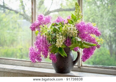 Bouquet Of Lilac In A Brown Clay Vase On A Window Sill