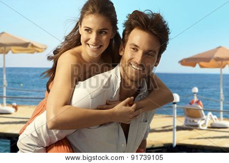 Happy casual caucasian couple playing piggyback at seaside summer holiday beach. Smiling, having fun.