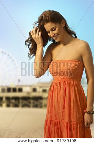 Happy young casual caucasian woman standing at the sandy summer beach. looking down. Smiling, copyspace.