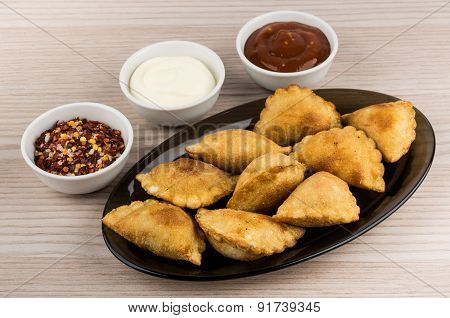 Pasties In Dish And Bowls  With Spices On Wooden Table