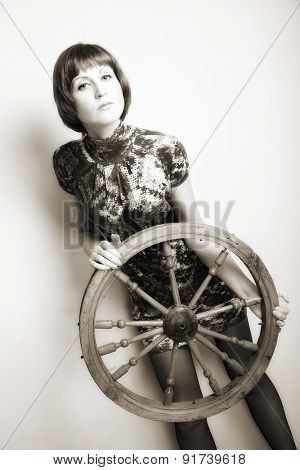 portrait of attractive woman with wooden wheel. indoor shot