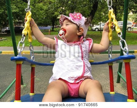 Small Child Rides On The Chain Swing