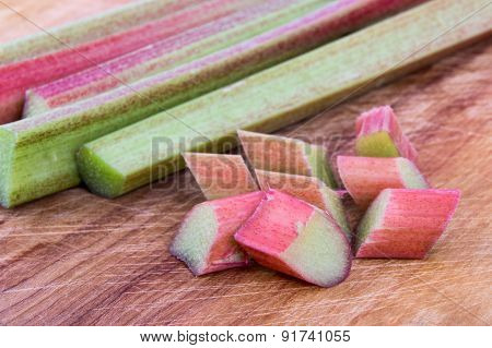 Fresh Rhubarb stalk and pieces on a wooden cutting board