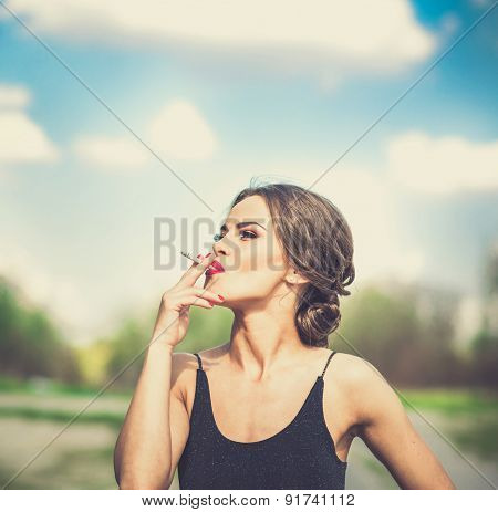 Pretty Woman In Black Dress Smoking Sigarette Outdoor