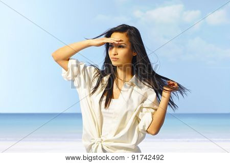 Portrait of attractive young Asian girl on the beach, shading eyes by hand.