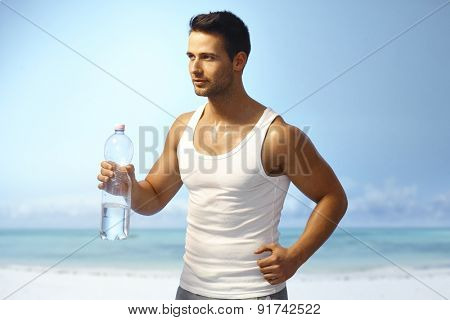 Handsome young man jogging on the coast, holding water bottle.