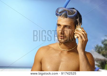 Handsome young scuba diver listening to seashell on the beach, looking away.