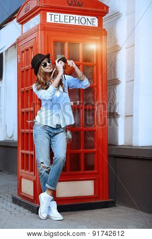 Beautiful young woman walking in the city and photograghs. Europe, England. Vacation, tourist trip.
