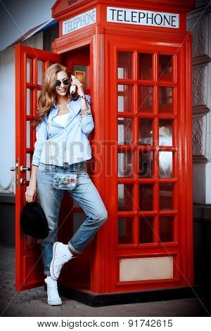 Pretty young woman talking on the phone in telephone booth. Europe, England. Vacation, tourist trip.