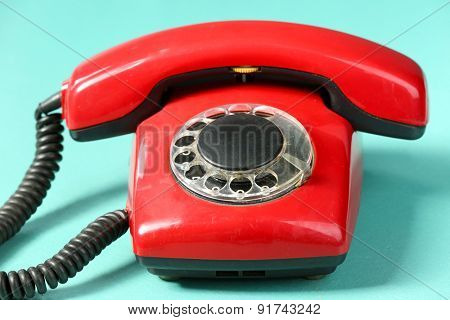 Retro red telephone on table on green background