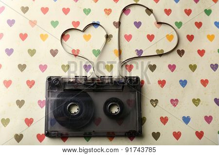 Audio cassette with magnetic tape in shape of hearts on paper background