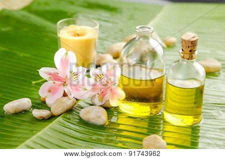 spa supplies with two orchid ,oil,yellow candle on banana leaf