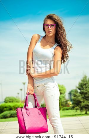 young woman in casual outfit  white jeans and top tank and pink bag outdoor in the city summer day