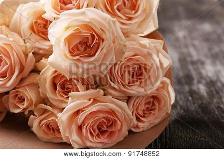 Bouquet of beautiful fresh roses wrapped in paper on wooden table, closeup