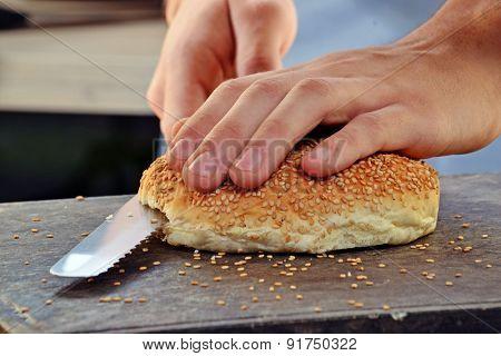 Slicing burger bread and preparing burger.
