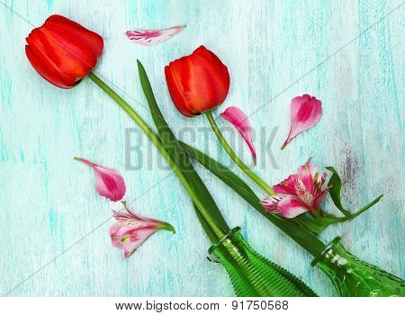 Beautiful red tulips in vases on wooden background