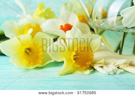 Fresh narcissus flowers on color wooden table, closeup