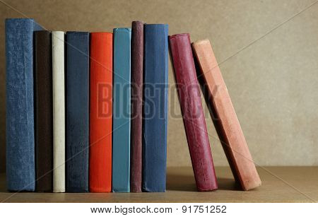 Old books on shelf, close-up, on wooden background