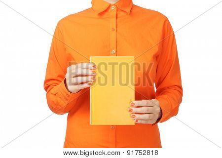 Woman in orange shirt holding a book